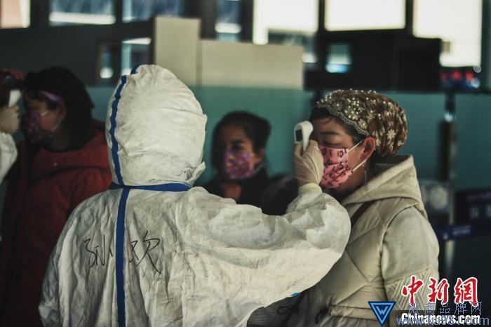图为工作人员对旅客检测体温。 受访单位供图 摄