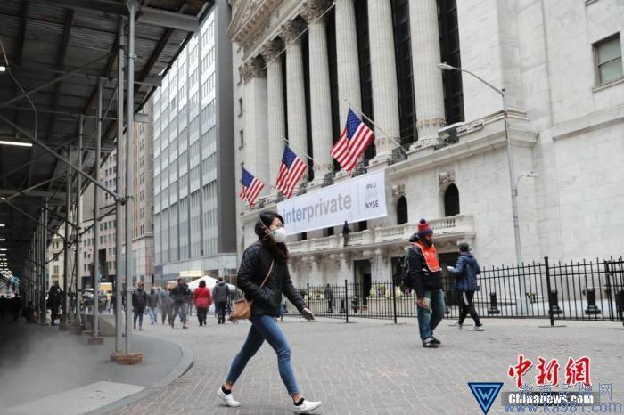 当地时间3月12日,一位戴口罩的民众走过纽约证券交易所。中新社记者 廖攀 摄