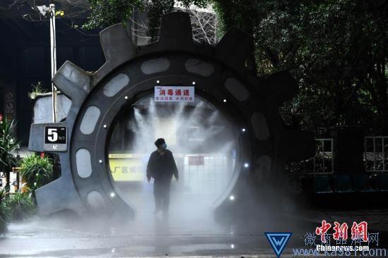2月10日,为做好复工疫情防控工作,在位于重庆南岸区一企业大门处,企业安装了自动喷雾消毒装置,为进出企业的员工进行全身消毒杀菌。图为企业员工经过喷雾消毒处。中新社记者 陈超 摄