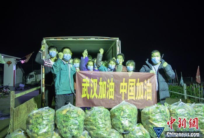 """张飞带领着大伙将基地的蔬菜打包装车,并打出""""武汉加油,中国加油""""的横幅。 张小东 摄"""