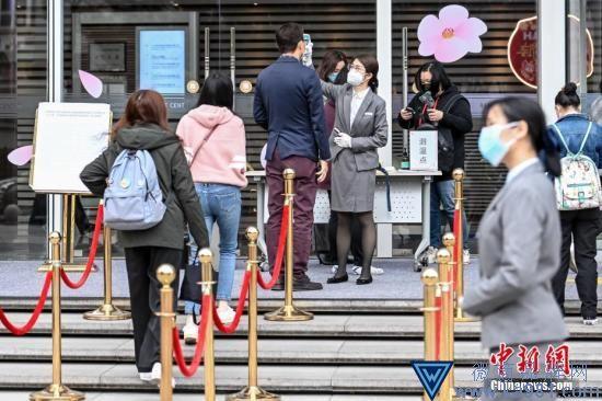 2月10日,复工首日的广州,珠江新城中央商务区一写字楼入口处设置体温检测点,工作人员为进入大楼的人员检测体温。中新社记者 陈骥旻 摄